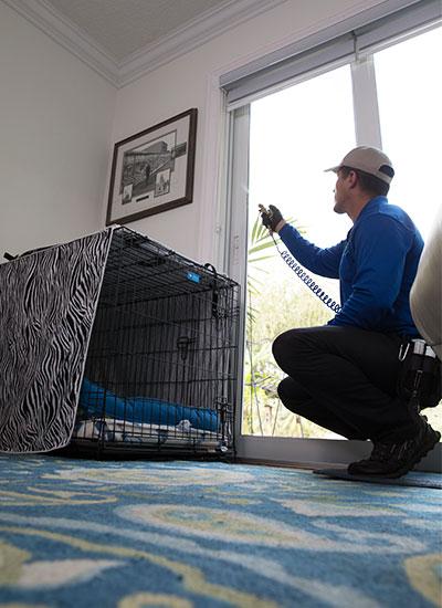 A flea control technician works inside a customer's home.